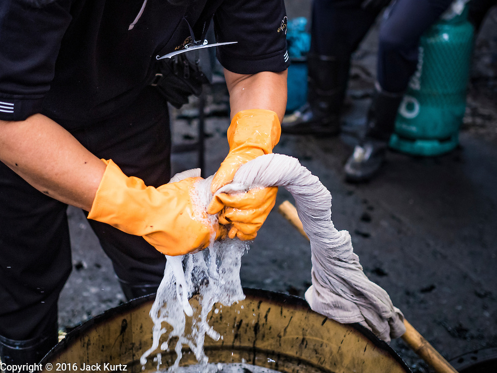 04 NOVEMBER 2016 - BANGKOK, THAILAND: A volunteer wrings out a shirt being dyed black at Krungthai Tractor. About 150 volunteers are working at Krungthai Tractor in Bangkok to dye clothes black for people in mourning following the death of Bhumibol Adulyadej, the King of Thailand. The government declared a one year mourning period, during which Thais are encouraged to wear black and a 30 day mourning period during which Thais are very strongly encouraged to wear black. Furthermore, black is mandatory for official mourning functions, including visits to the Grand Palace and Sanam Luang, the public ceremonial ground across the street from the Palace. The expectation to wear black created a shortage of black clothes in many markets and Thailand's poor couldn't afford what black clothes were still available. Community groups have started dyeing clothes for people who either can't find or can't afford black clothes. The clothes dyeing volunteers at Krungthai Tractor were organized by Thai actress Chompoo Araya A. Hargate and Thai fashion blogger Chavaporn Laohapongchana.      PHOTO BY JACK KURTZ