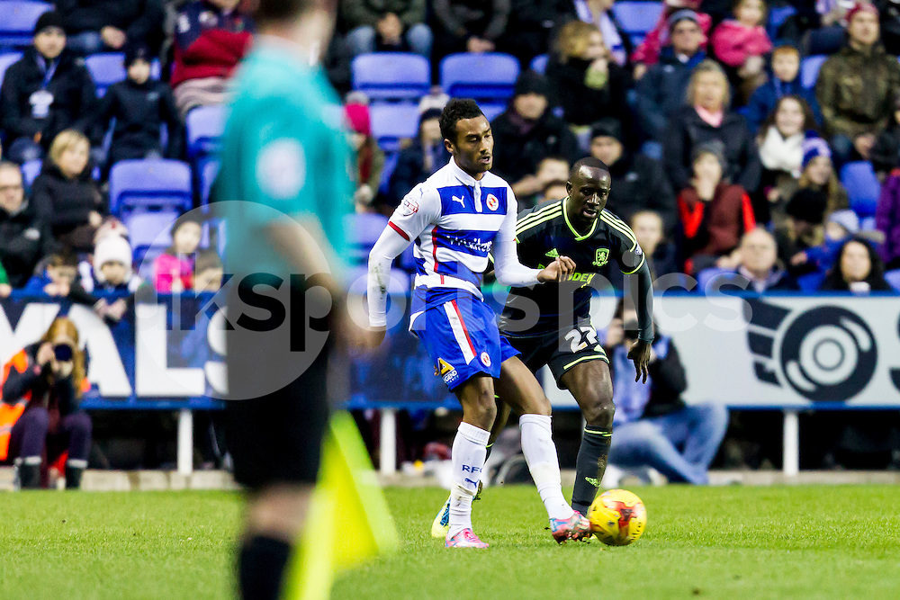 Jordan Obita of Reading passes the ball while under pressure from Albert Adomah of Middlesbrough (27) during the Sky Bet Championship match between Reading and Middlesbrough at the Madejski Stadium, Reading, England on 10 January 2015. Photo by Gareth  Brown.