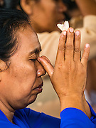16 JULY 2016 - UBUD, BALI, INDONESIA: A Balinese Hindu woman prays Saturday before the mass cremation. Local people in Ubud exhumed the remains of family members and burned their remains in a mass cremation ceremony Wednesday. Almost 100 people were cremated and laid to rest in the largest mass cremation in Bali in years this week. Most of the people on Bali are Hindus. Traditional cremations in Bali are very expensive, so communities usually hold one mass cremation approximately every five years. The cremation in Ubud concluded Saturday, with a large community ceremony.     PHOTO BY JACK KURTZ