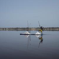 Un homme dirige sa barque vers le bord du lac pour recharger sa cargaison de sel.