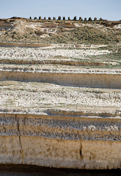 """Cliff formations in the vast Wadi Haynun, near the UNESCO """"Land of Frankincense"""" preservation area, Dhofar, Oman.  A row of tri-lobed pre-Islamic Arab tombs line the top above the horizontal layers stepping below."""