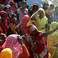 Asia, India, Rajasthan. Women in colorufl saris dance on the street.
