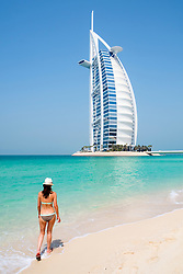 Woman walking on beach at Burj Al Arab luxury hotel in Dubai United Arab Emirates