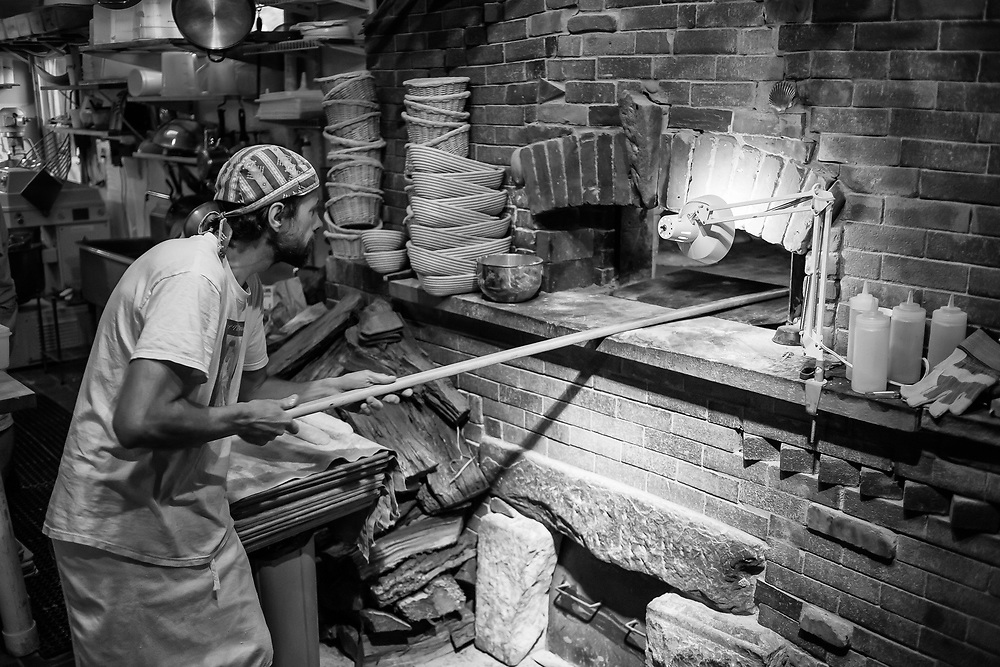 Andrea Colognese of The Village Hearth Bakery checking on loaves of bread in the oven. Colognese built his oven himself, and the details show—the brickwork details below the hearth, the keystone above the oven door, the hearthstone itself.