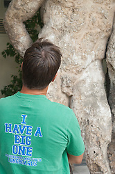 "man in a tee shirt ""I have a big one"" looking at greek statue"
