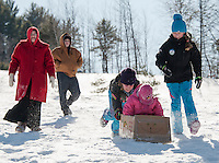 Sarah Piper gets a push from Sophia Lehr and Abby Jarvi during Gilford Parks and Recreation Cardboard Derby race the the Outing Club sledding hill Wednesday morning.  (Karen Bobotas/for the Laconia Daily Sun)