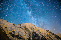 A wide angle perspective photograph on a starry Summer sky above Aiguille de Bionnassay, Les Houches, France.