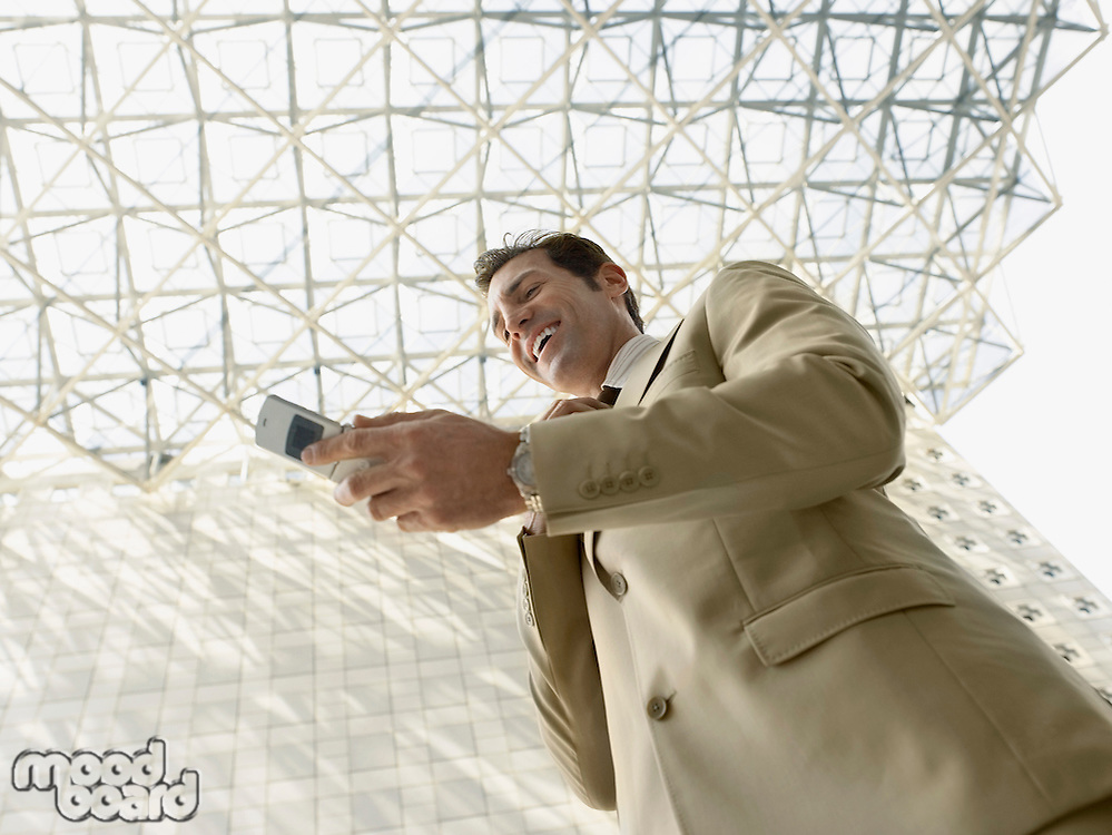 Low angle view of businessman using mobile phone