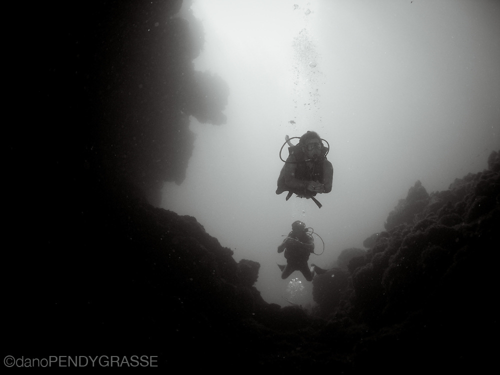 Divemaster Pete leads divers into spooky channel in Roatn, Honduras.