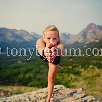 woman yoga pose on boulder big mountain background, glacier national park