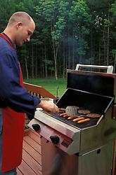 Food Food suburban man male cooks hot dogs hamburgers on  backyard bbq grill