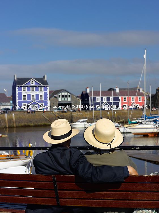 View across harbour to Harbourmaster Hotel (over seated couple wearing hats)<br /> Aberaeron<br /> Ceredigion<br /> Mid<br /> Towns &amp; Villages