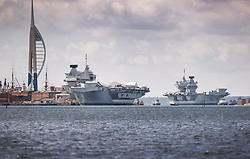 © Licensed to London News Pictures. 02/07/2020. Portsmouth, UK. Royal Navy aircraft carrier HMS Queen Elizabeth (R) is seen next to her sister ship HMS Prince of Wales as she enters Portsmouth harbour. The 65,000 tonne supercarrier has been at sea for 10 weeks conducting trials of the new F35 Lightening fighter jets ahead of her first operational mission in 2021. Photo credit: Peter Macdiarmid/LNP