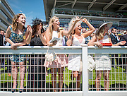 © Licensed to London News Pictures. 06/06/2014. Epsom, UK. A group of women cheer on their horse in The Princess Elizabeth Stakes. Ladies Day today 6th June 2014 at Epsom 2014 Investic Derby Festival in Surrey. Traditionally, elegant, fashionable racegoers gather for a classic day's racing at Epsom Racecourse, Surrey. Photo credit : Stephen Simpson/LNP