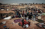After leaving Libya, Bengladesh migrant workers prepare to move on after spending the night in a makeshift camp next to Tunisia's Ras Jdir border station. 04 March 2011.