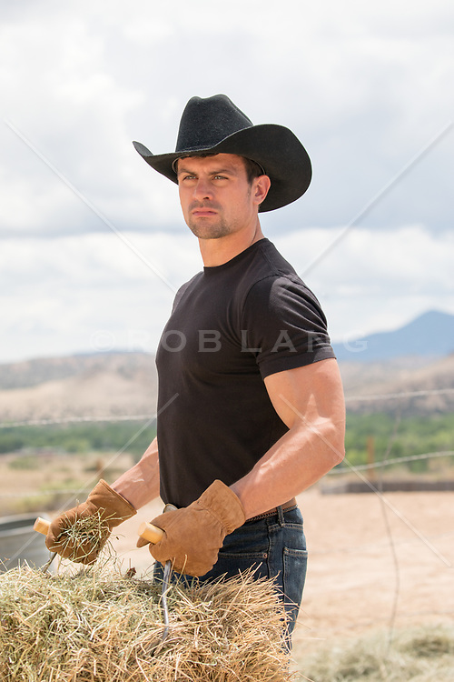 cowboy carrying a hay bale on a ranch