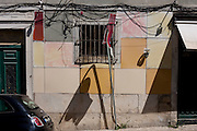 A tangle of confusing wires and cables and shadows on a house's frontage in Bairro Alto, Lisbon, Portugal.