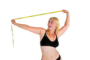 Young woman laughs at a tape measure. She has overcome compulsive body analysis caused by body image disorder such as anorexia nervosa. Model released