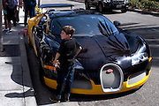 A boy is standing for a picture next to a Bugatti car parked along Rodeo Drive, the renowned shopping avenue running across Beverly Hills, Los Angeles, California, USA.