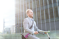 Businessman riding bicycle outside office building