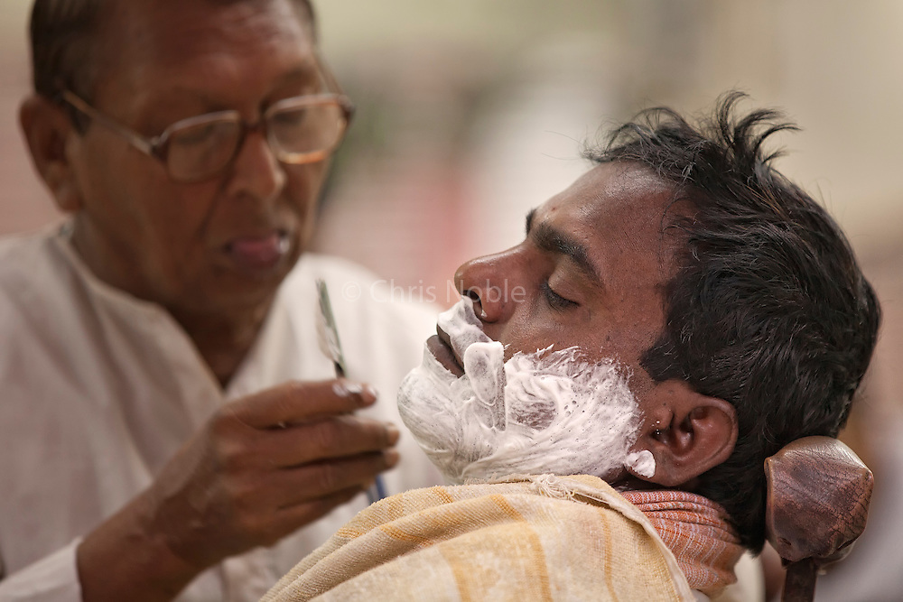 A man receives a shave from a barber in the Old City of Varanasi India.