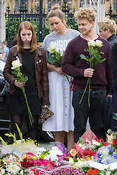 Parliament Square, Westminster, London, June 17th 2016. Following the murder of Jo Cox MP friends and members of the public lay flowers, light candles and leave notes of condolence and love in Parliament Square, opposite the House of Commons. PICTURED: Three young people, clutching white roses and visibly moved look at the growing array of floral tributes.