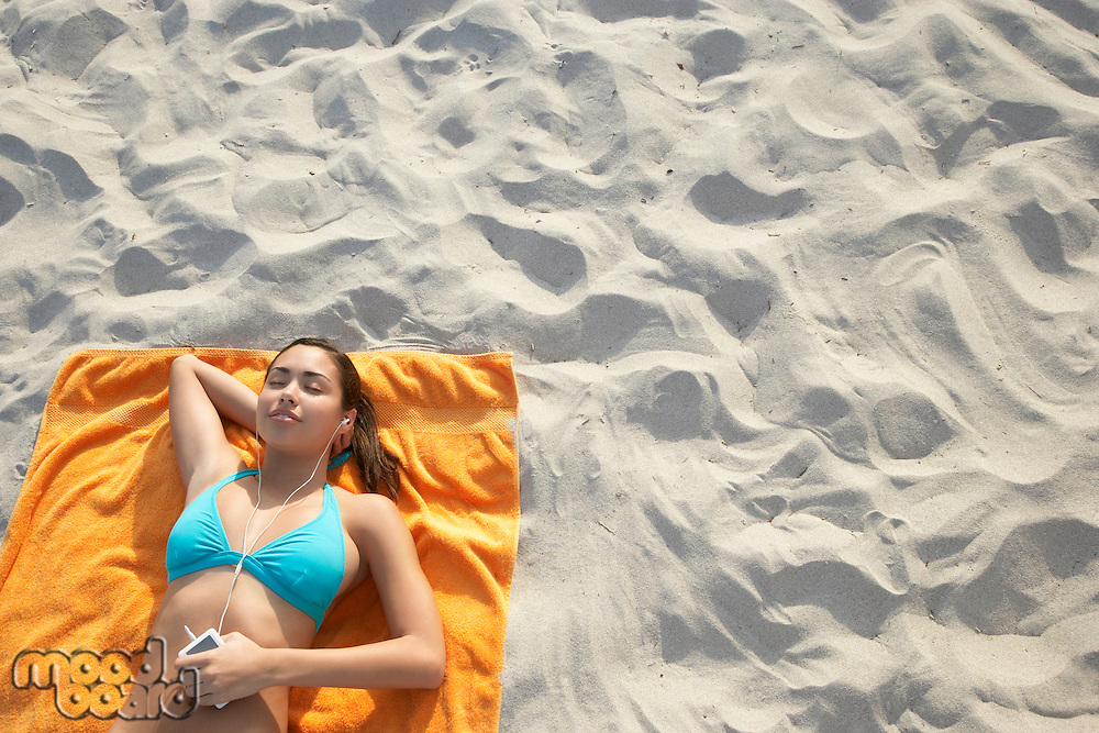 Teenage girl (16-17) using mp3 player lying on beach view from above