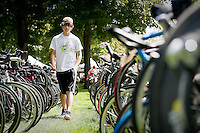 JEROME A. POLLOS/Press..Devin Lewis, 15, walks between the rows of hundreds of bicycles he helped unload Thursday for TriBike Transport in the Ironman Village.