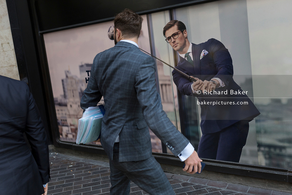 A Londoner walk past a closed shop poster featuring a businessman wearing a blue suit - a favoured style and colour of menswear in the City of London, the capital's financial district - aka the Square Mile, on 29th August 2018, in London, England.