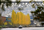 A boat heads west along the ship canal just west of the Fremont Bridge. The Aurora Bridge looms in the distance. (Mike Siegel / The Seattle Times)