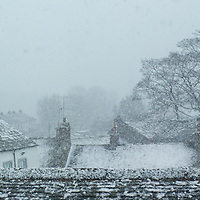 Snowy slate rootops and trees in a traditional Cumbrian village