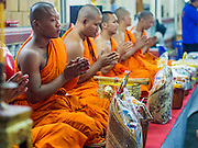 """07 MARCH 2015 - NAKHON CHAI SI, NAKHON PATHOM, THAILAND: Buddhist monks lead a chanting service during the Wat Bang Phra tattoo festival. Wat Bang Phra is the best known """"Sak Yant"""" tattoo temple in Thailand. It's located in Nakhon Pathom province, about 40 miles from Bangkok. The tattoos are given with hollow stainless steel needles and are thought to possess magical powers of protection. The tattoos, which are given by Buddhist monks, are popular with soldiers, policeman and gangsters, people who generally live in harm's way. The tattoo must be activated to remain powerful and the annual Wai Khru Ceremony (tattoo festival) at the temple draws thousands of devotees who come to the temple to activate or renew the tattoos. People go into trance like states and then assume the personality of their tattoo, so people with tiger tattoos assume the personality of a tiger, people with monkey tattoos take on the personality of a monkey and so on. In recent years the tattoo festival has become popular with tourists who make the trip to Nakorn Pathom province to see a side of """"exotic"""" Thailand.   PHOTO BY JACK KURTZ"""