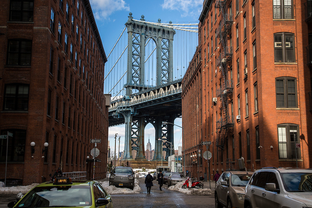 The Empire State Building framed by Manhattan Bridge which is framed by the red brick buildings of Washington Street, Dumbo, Brooklyn, New York City, United States of America.  People walk across the street, which still has cars surrounded in snow.  (photo by Andrew Aitchison / In pictures via Getty Images)
