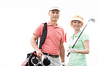Portrait of happy male and female golfers standing against clear sky