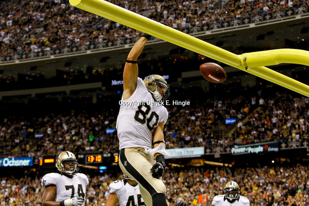 September 23, 2012; New Orleans, LA, USA; New Orleans Saints tight end Jimmy Graham (80) dunks over the goal post after scoring a touchdown against the Kansas City Chiefs  during the third quarter of a game at the Mercedes-Benz Superdome. The Chiefs defeated the Saints 27-24 in overtime. Mandatory Credit: Derick E. Hingle-US PRESSWIRE
