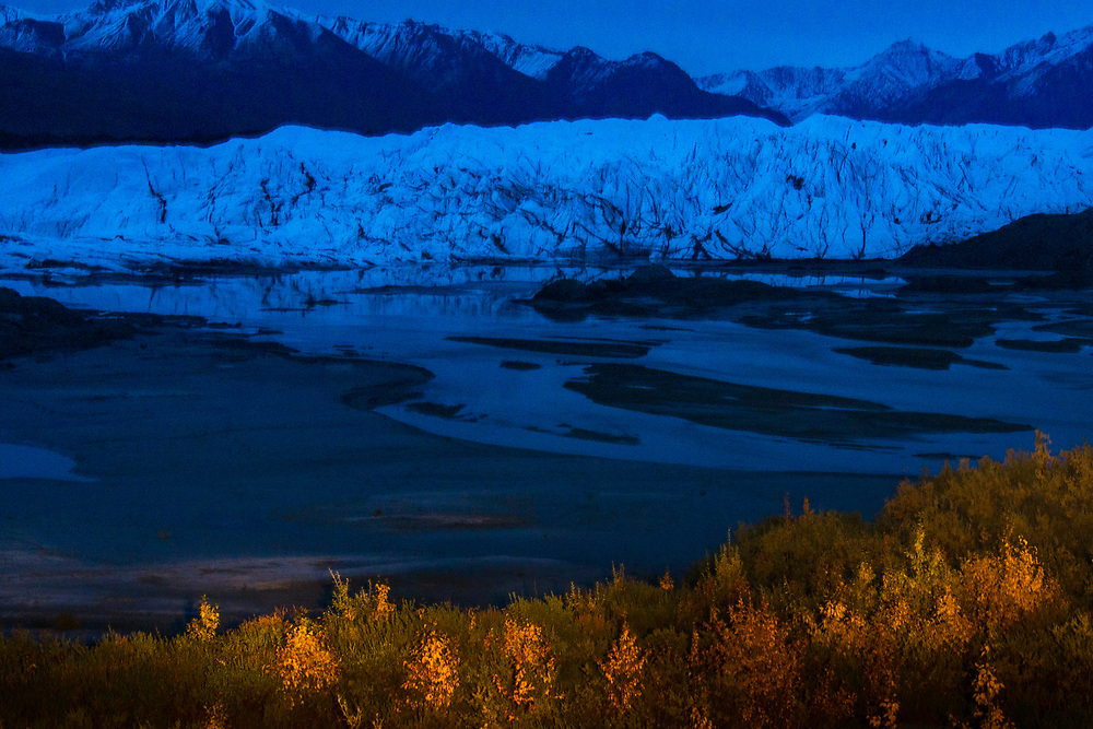 Night photography of the an Alaskan glacier and river with light painted trees in the foreground.