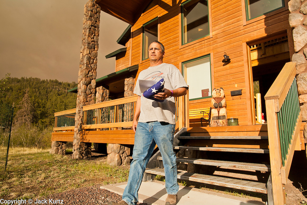 "04 JUNE 2011 - GREER, AZ: An American flag was the last thing Jim Tress (CQ) grabbed from his home in Greer before evacuating back to Tucson. The fire grew to more than 140,000 acres early Saturday with zero containment. A ""Type I"" incident command team has taken command of the fire.    PHOTO BY JACK KURTZ"