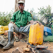 Kabanda Epimaque repairs damaged jerry cans for villagers on the side of the road in Rulindo, Rwanda. In Rwanda, jerry cans are used multiple times per day by families to haul water from village taps and communal water sources to their homes. Kabanda charges between 30 and 200 Rwandan francs (roughly $0.05 to $0.35), depending upon the size of the hole, per repair.