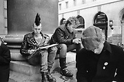 Punks sitting and man in cap at Stop The City demonstration, London, 1983.