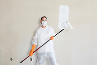 Portrait of female worker in protective workwear holding a paint roller