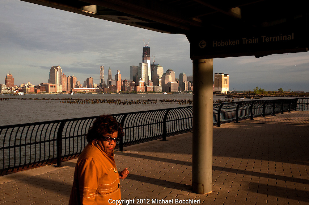 HOBOKEN, NJ - APRIL 30:  Commuters walk to the Hudson-Bergen Light Rail station as construction continues at the top of One World Trade Center to make it New York City's tallest building on April 30, 2012 as seen from 1 Hudson Place in Hoboken, New Jersey. One World Trade Center is being built to replace the twin towers destroyed in the Sept. 11 attacks. It reached just over 1,250 feet today making it just taller than the observation deck on the Empire State Building.  (Photo by Michael Bocchieri/Bocchieri Archive)