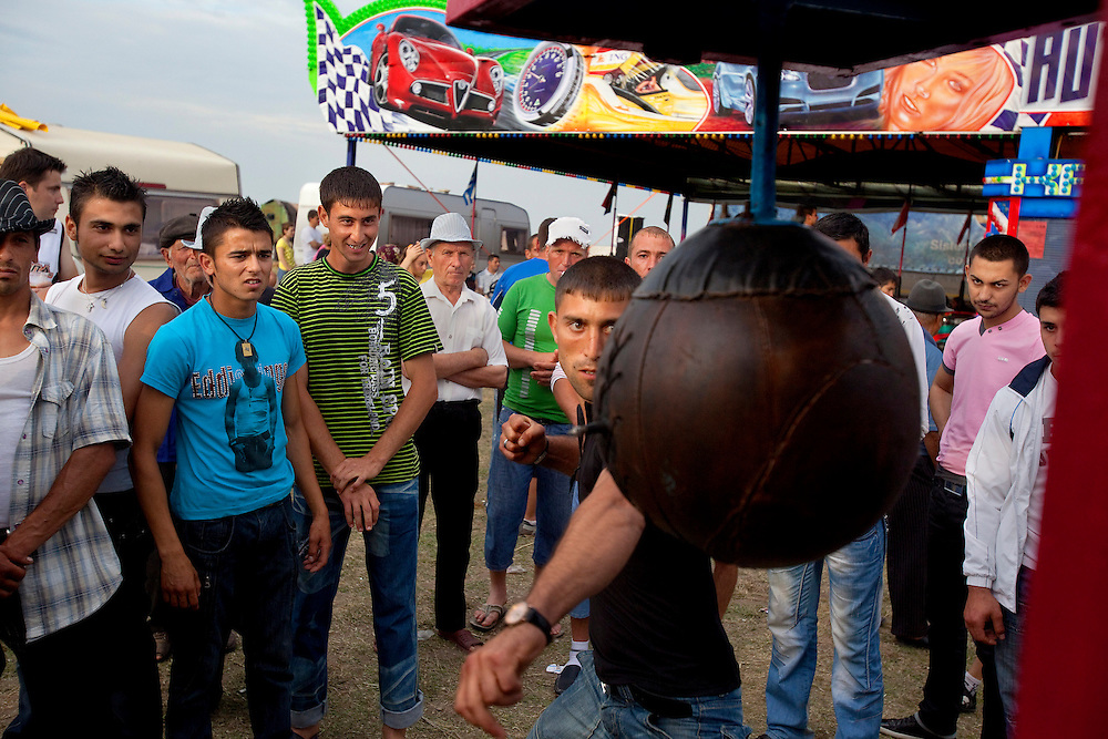 Young men test their strength at the local fair in Alexandria, near Buzescu, a small town in Romania.