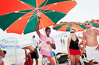 """Mellieha, Malta - 19 August, 2012:  Hassan Mahamed Dalmar, 21, an immigrant from North Somalia, places an umbrella for a couple of tourists in Mellieha Bay, Malta, on 19 August, 2012. Hassan left Somalia in 2007 and went to Djibouti, Eritrea, Sudan, Libya and arrived in Malta in 2009 after paying a smuggler $900 to board a boat with 160 immigrants. After 7 days, the boat had finished its gas, food and water. They were saved by a Finnish ship that brought them to Malta. A finnish worker who helped Hassan told him: """"You are born again now. Pray the Lord and start a new life"""". Upon his arrival in Malta he was put in a detention center for 12 months. His application for refugee status was rejected. He made it to Belgium in August 2011 and was deported back to Malta in January 2012. Upon his return he was imprisoned for 4 months for traveling illegally. He was released on May 28, 2012. Since then he has been working, sleeping outdoors and living in the beach of Mellieha Bay, where he sets up umbrellas and sunbeds from 6:30am to 7:30pm.<br /> <br /> Some immigrants work, live, sleep and eat for the entire summer season in the Maltese beaches. Their work consists of waking up at 6:30am and unpile and place sunbeds, cushions and umbrellas at the beach before tourists arrive. Upon their arrival at the beach, tourists are guided by the migrants to the spot they choose. Umbrellas and sunbeds cost 5 euros each. The toursts pay the migrants, whom brings the money to the owner. Each migrant is paid 25 euros a day. By 9am, there are about 90 umbrellas and 180 sunbeds ready for the tourists.<br /> <br /> Gianni Cipriano for The New York Times"""