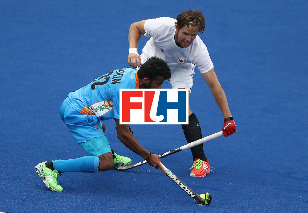 RIO DE JANEIRO, BRAZIL - AUGUST 12:  Adam Froese #14 of Canada defends Chandanda Thimmaiah #32 of India during a Men's Preliminary Pool B match on Day 7 of the Rio 2016 Olympic Games at the Olympic Hockey Centre on August 12, 2016 in Rio de Janeiro, Brazil.  (Photo by Sean M. Haffey/Getty Images)