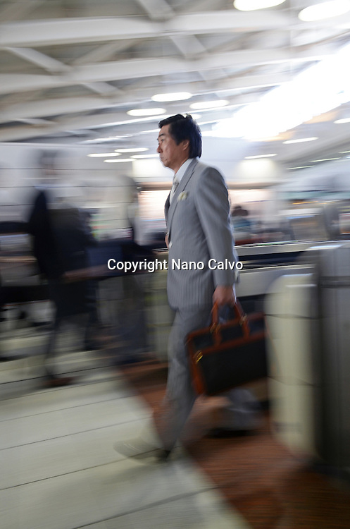 Thousands of businessmen using subway and train services during Rush Hour, Tokyo