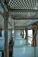 Le Ferrovie del Sud Est nascono in Puglia, nell'ottobre del 1931. A questà nuova società veniva dato in concessione l'insieme delle reti ferroviarie precedentemente gestite da diversi organismi (Società per le Ferrovie Salentine, Società per le Ferrovie Sussidiate, Ferrovie dello Stato)..Le aree pugliesi attraversate dalla società ferroviaria sono l'area barese, la fascia Taranto-Brindisi e l'area leccese-salentina, collegando fra loro i capoluoghi di Bari, Taranto e Lecce, nonché oltre 130 comuni delle province meridionali..Il reportage fotografico sulle Ferrovie Sud Est intende testimoniare l'evoluzione tecnologica che, durante gli anni, ha modificato e migliorato il servizio ferroviario e la convivenza del progresso con tracce del passato, attraverso un viaggio tra le stazioni e i depositi..Portabagagli nella 2° classe di un Carminati.