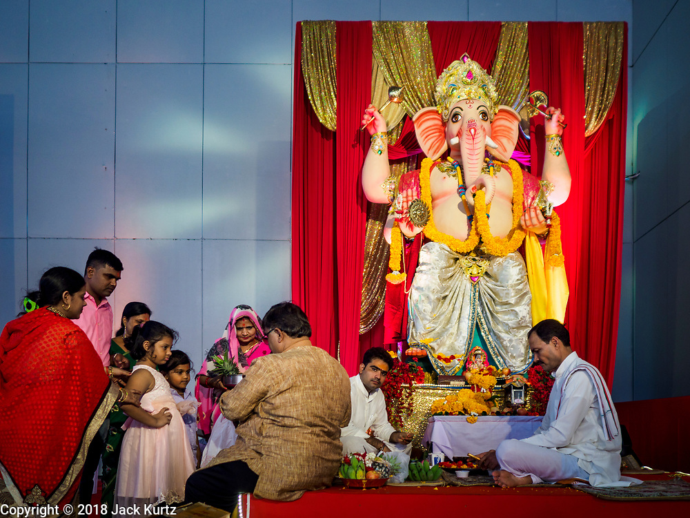 """23 SEPTEMBER 2018 - BANGKOK, THAILAND:  A family gets blessings at the Ganesha Festival at Wat Dan in Bangkok. Ganesha Chaturthi also known as Vinayaka Chaturthi, is the Hindu festival celebrated on the day of the re-birth of Lord Ganesha, the son of Shiva and Parvati. The festival, also known as Ganeshotsav (""""festival of Ganesha"""") is observed in the Hindu calendar month of Bhaadrapada, starting on the the fourth day of the waxing moon. The festival lasts for 10 days, ending on the fourteenth day of the waxing moon. Outside India, it is celebrated widely in Nepal and by Hindus in the United States, Canada, Mauritius, Singapore, Thailand, Cambodia, and Burma.  PHOTO BY JACK KURTZ"""