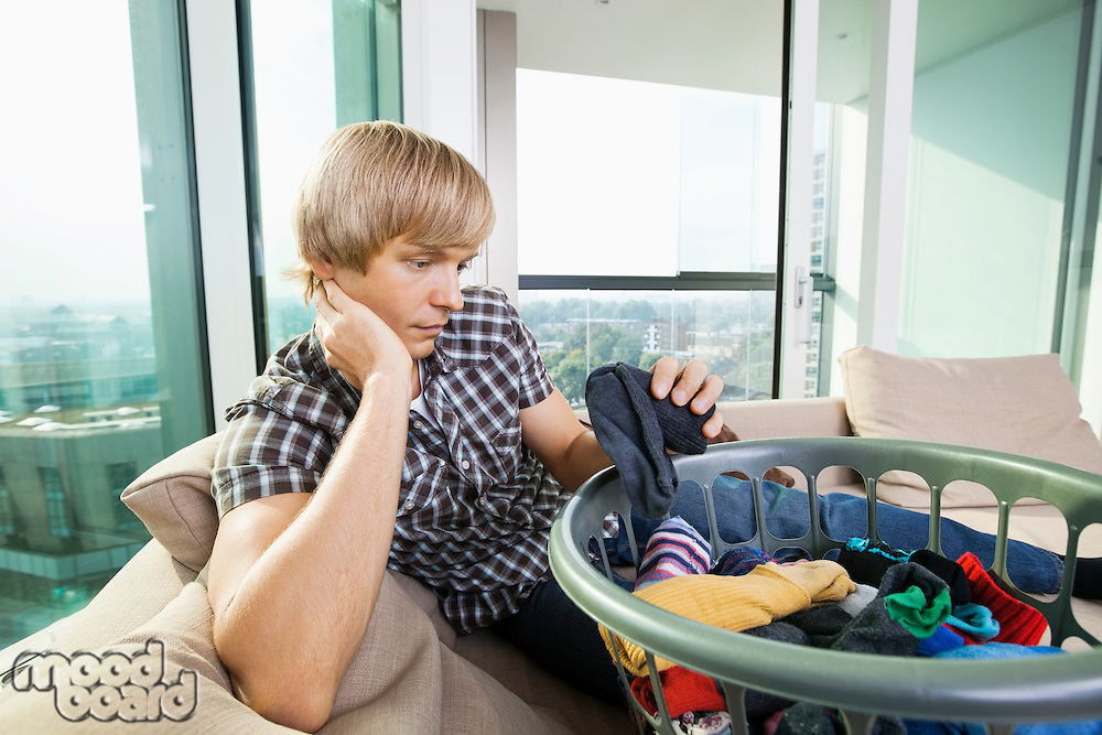 Tired man with laundry basket sitting on sofa at home