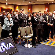 Man speaks to a large group of men and women in a business presentation