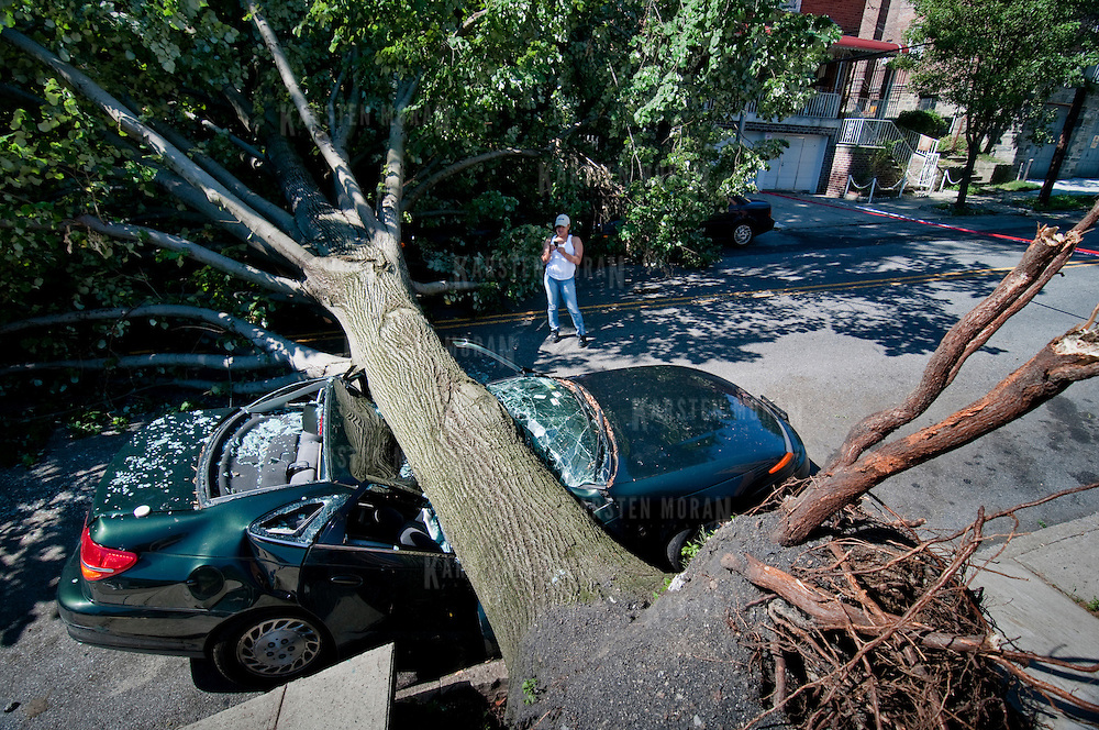 July 26, 2010 - Bronx, NY : A passerby photographs a massive tree resting atop a green saturn, parked on Orloff Avenue near Van Cortlandt Park West in Kingsbridge Heights on Monday morning. The aftermath of the July 25 storm, which wreaked havoc on North Riverdale. Photos by Karsten Moran / The Riverdale Press